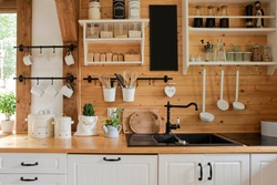 Interior of kitchen in rustic style with vintage kitchen ware and wooden wall. White furniture and wooden decor in bright cottage indoor.