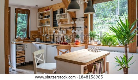 Interior of kitchen in vintage rustic style with wooden furniture in a cottage. Bright indoors in a cozy kitchen with window and plant.  Foto stock ©