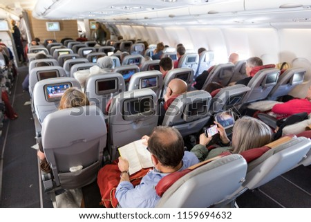 Interior of large commercial airplane with unrecognizable passengers on their seats during flight.