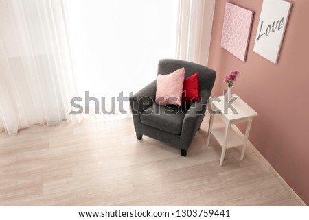 Interior of light room with cozy armchair near window #1303759441