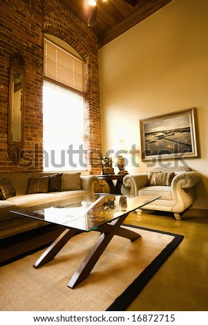 Interior of living room with large window, brick wall, coffee table, and sofa.
