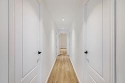 Interior of long narrow hallway with closed doors, wooden floor and white walls in apartment designed in minimal style.