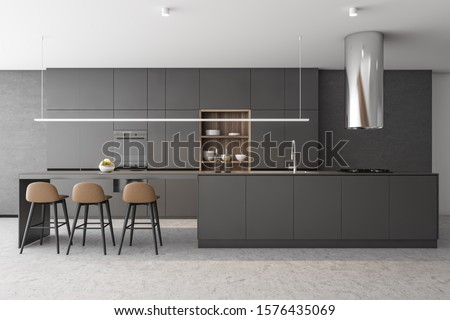 Interior of luxury kitchen with concrete walls and floor, dark gray island with built in sink and cooker, gray cupboards and bar with stools. 3d rendering