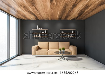 Interior of luxury living room with grey walls, marble floor, comfortable beige sofa standing near round coffee table and shelves with vases. Window with blurry cityscape. 3d rendering