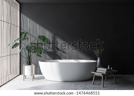 Interior of minimalistic bathroom with gray walls, concrete floor, light wooden blinds, comfortable white bathtub and chair with towels. 3d rendering