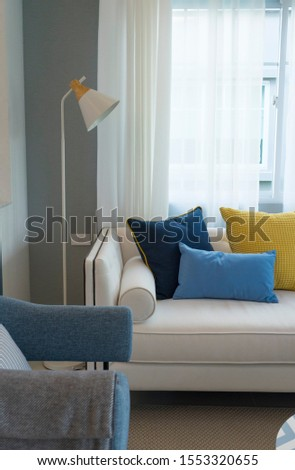Interior of minimalistic living room with white sofa, yellow, blue cushion AND FLOOR LAMP. #1553320655
