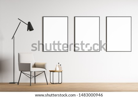 Interior of minimalistic living room with white walls, wooden floor, comfortable white armchair near coffee table and three vertical mock up poster frames. 3d rendering
