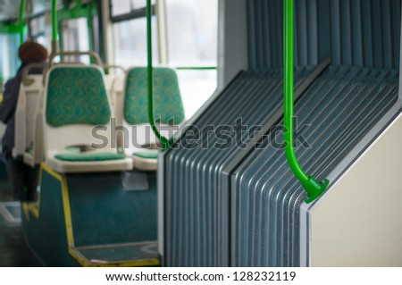 Interior of modern articulated bus. Seat places in front side of bus. Focus on articulated joint part