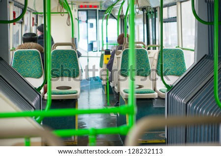 Interior of modern articulated bus. Seat places in front side of bus. Shoot through articulated joint part
