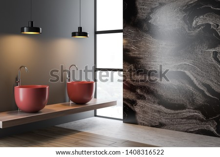 Interior of modern bathroom with gray and marble walls, wooden and concrete floor, narrow window, two red sinks standing on wooden shelf and ceiling lamps hanging above them. 3d rendering