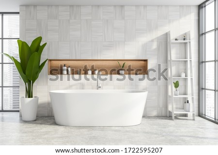 Interior of modern bathroom with white wooden walls, concrete floor, comfortable bathtub with niche above it and shelves with cosmetic products. Windows with blurry cityscape. 3d rendering Stock photo ©