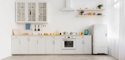Interior of modern comfortable kitchen. Multicolored cups and teapot, orange juice in glass and utensils on white furniture, refrigerator, flowers in pots on shelves, light wall in daylight, panorama