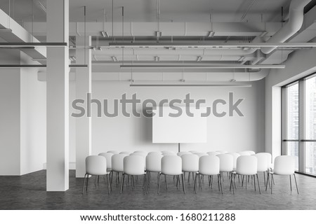 Interior of modern industrial style office lecture hall with white walls, concrete floor, rows of white chairs and mock up projection screen. Concept of presentation and education. 3d rendering