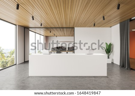 Interior of modern office hall with white and orange walls, concrete floor, comfortable white reception desk with two laptops on it and open space area in background. 3d rendering Zdjęcia stock ©