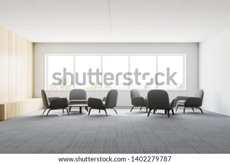 Interior of modern office lounge with white and wooden walls, carpeted floor and soft gray armchairs standing near round coffee tables. Windows with tropical view. 3d rendering