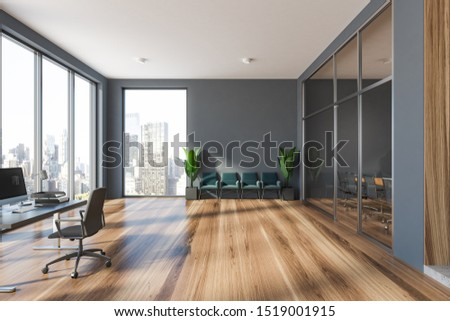 Interior of modern office waiting room with gray walls, wooden floor, row of green armchairs and computer table with armchair. 3d rendering