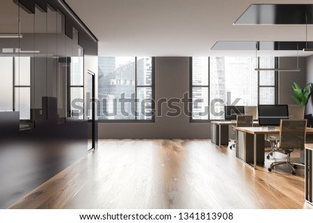 Interior of modern office with gray, black and glass walls, wooden floor, big windows and rows of wooden and gray computer tables. 3d rendering