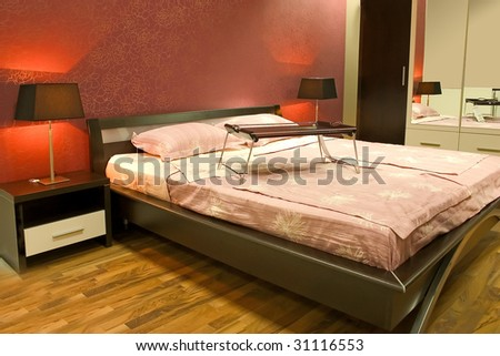 Interior of modern red bedroom with furniture and lamps