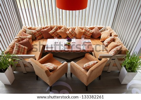 Interior of modern restaurant with a big orange sofa two orange chairs, an orange lamp and the laid table.Top view