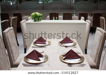 Interior of modern restaurant with served table for four people