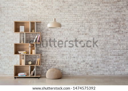 Interior of modern room with bookcase, pouf and lamp Stockfoto ©