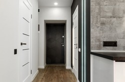 Interior of new empty apartment, long home corridor with parquet floor, white wall and doors, copy space. Entrance corridor