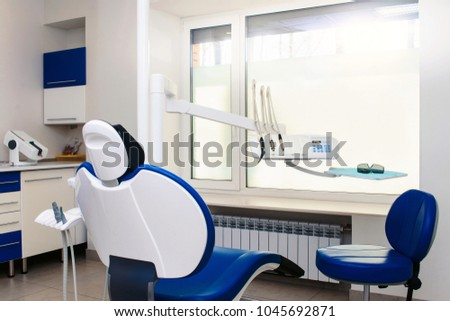 Interior of new modern dental clinic office room with chair in blue and white colors. Dentistry, stomatology, medicine medical equipment concept in teeth cabinet