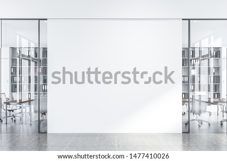Interior of office hall with white walls and glass door meeting room with long wooden table with white chairs and bookcases with folders. Mock up wall in the center. 3d rendering