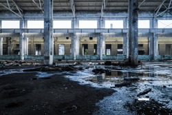 Interior of old factory buildings destroyed. Ruins of industrial enterprise, dark debris destroyed factory premises in factory as result of economic crisis and earthquake.