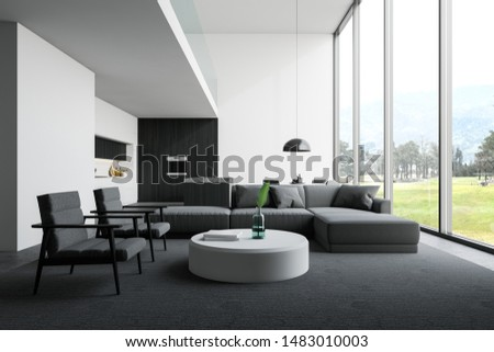 Interior of open plan room with living room area with gray sofa and armchairs near round coffee table and kitchen with white and dark wooden walls, island, countertops and table. 3d rendering