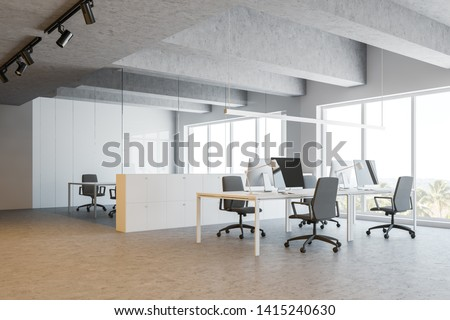 Interior of open space office with white walls, concrete floor and ceiling, white computer tables and meeting room behind glass walls. 3d rendering