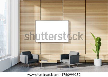 Interior of panoramic corporate office waiting room with white and wooden walls, concrete floor, two comfortable gray armchairs and TV with mock up screen. Blurry cityscape. 3d rendering