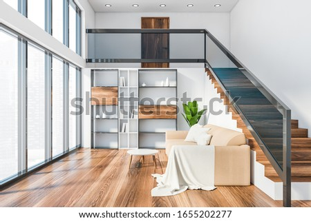 Interior of panoramic living room with white walls, wooden floor, beige sofa with bookcase near it and staircase. Window with blurry cityscape. 3d rendering