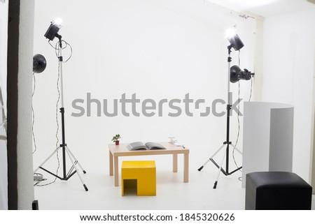 Interior of Photographic Studio. Spotlight, Tripod, and White Background Set in a Minimalist Sapce.