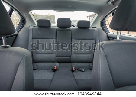 Interior of premium sedan car. Salon with seats, electronics, gauges, buttons, steering, mirrors and windows. Wooden panel and glass hatch. #1043946844