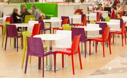 Interior of public dining area with colourul plastic chairs and tables