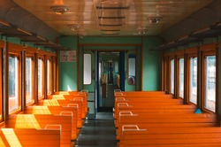Interior of railway passenger carriage. Vintage atmosphere. Wooden benches and historic railway design. Old car inside
