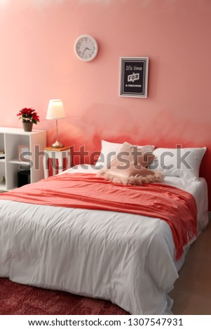 Interior of room with comfortable bed near pink wall