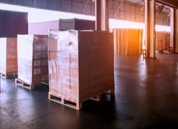 Interior of shipping warehouse area, stack of package boxes wrapping plastic on pallet, freight industry delivery logistics and transport