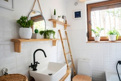 Interior of small bathroom with window, wooden decoration, shelf and ladder. Stylish wash basin and tap, round mirror on a white wall and plants on a shelf. Rustic bathroom in a cottage in rural style