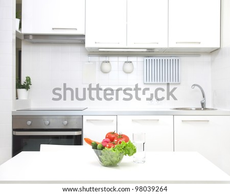 interior of small white kitchen with fresh vegetables on the table