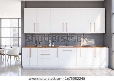 Interior of spacious panoramic kitchen with grey walls, tiled floor, white countertops and cupboards and dining table with armchairs in background. 3d rendering Stock photo ©