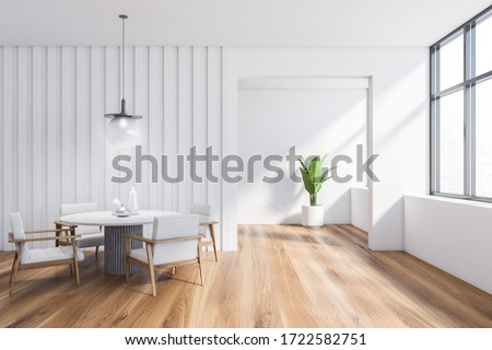 Interior of stylish dining room with white walls, wooden floor, comfortable round table with white armchairs and potted plant in background. Window with blurry cityscape. 3d rendering