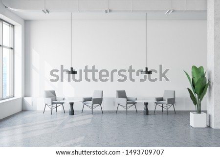 Interior of stylish industrial style office waiting room with white walls, concrete floor, gray armchairs near round coffee tables and small cabinets. 3d rendering