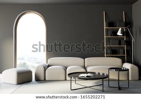 Interior of stylish living room with gray walls, concrete floor, comfortable white sofa with round coffee tables standing near arched window and bookcase in background. 3d rendering