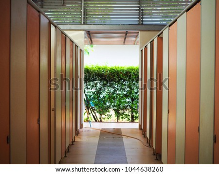 Interior of Thai public restroom in rural gas station, white wall, many brown pink doors, wet ceramic floor as center trail walkway with toilet on both side, high ceiling, sunlight green tree garden #1044638260