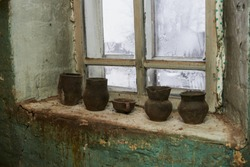 Interior of the abandoned house. You can see the shelf and the abandoned and dusty vessels. The house is an old house with clay walls.