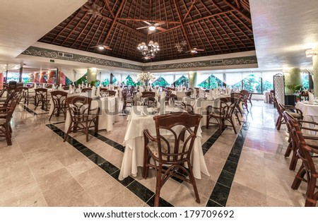 Interior of the caribbean, tropical restaurant with nicely served tables of the luxury five stars resort. Bahia Principe, Riviera Maya, Mexico.