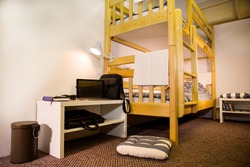 Interior of the hostel bedroom. Hostel with wooden bunk beds