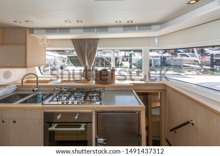 Interior of the luxury sailing catamaran - salon and cabin. Large and bright lounge with galley. Spacious cabin with high double bed and bright interior. Finishing with light wood VIP yachts Stockfoto ©